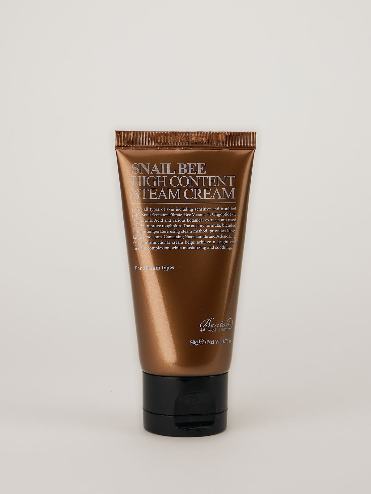 Benton Snail Bee High Content Steam Cream Feuchtigkeitspflege in glänzender bronzefarbener Tube mit schwarzem Deckel.